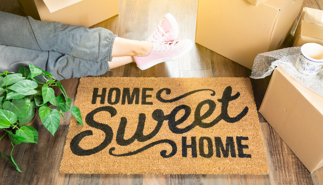 woman wearing sweats relxaxing near home sweet home welcome mat, moving boxes and plant
