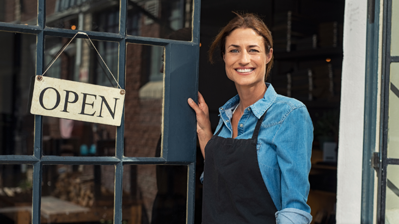 woman in front of business open sign