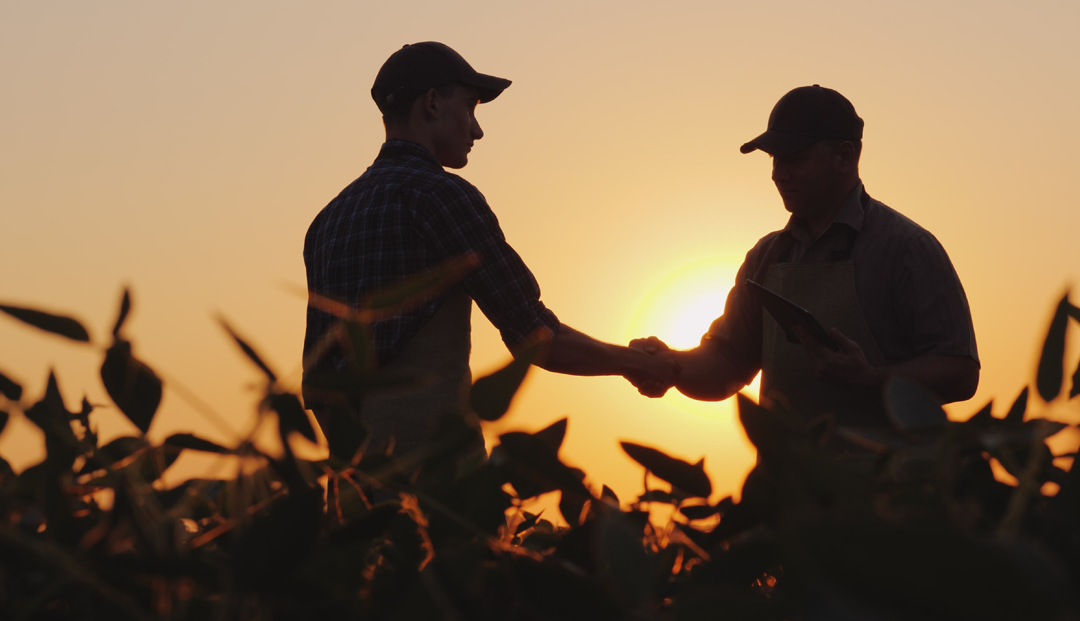 Farmer and Ag Banker standing in field shaking hands
