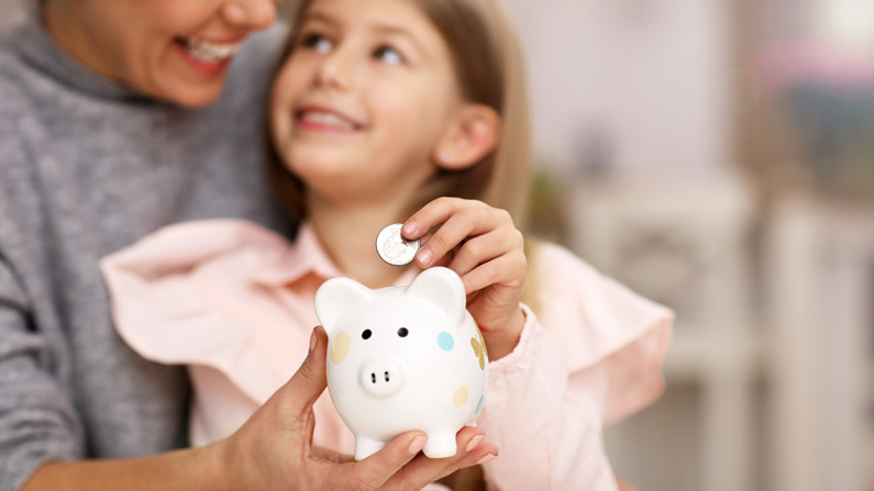 Mom and daughter putting coins in piggy bank