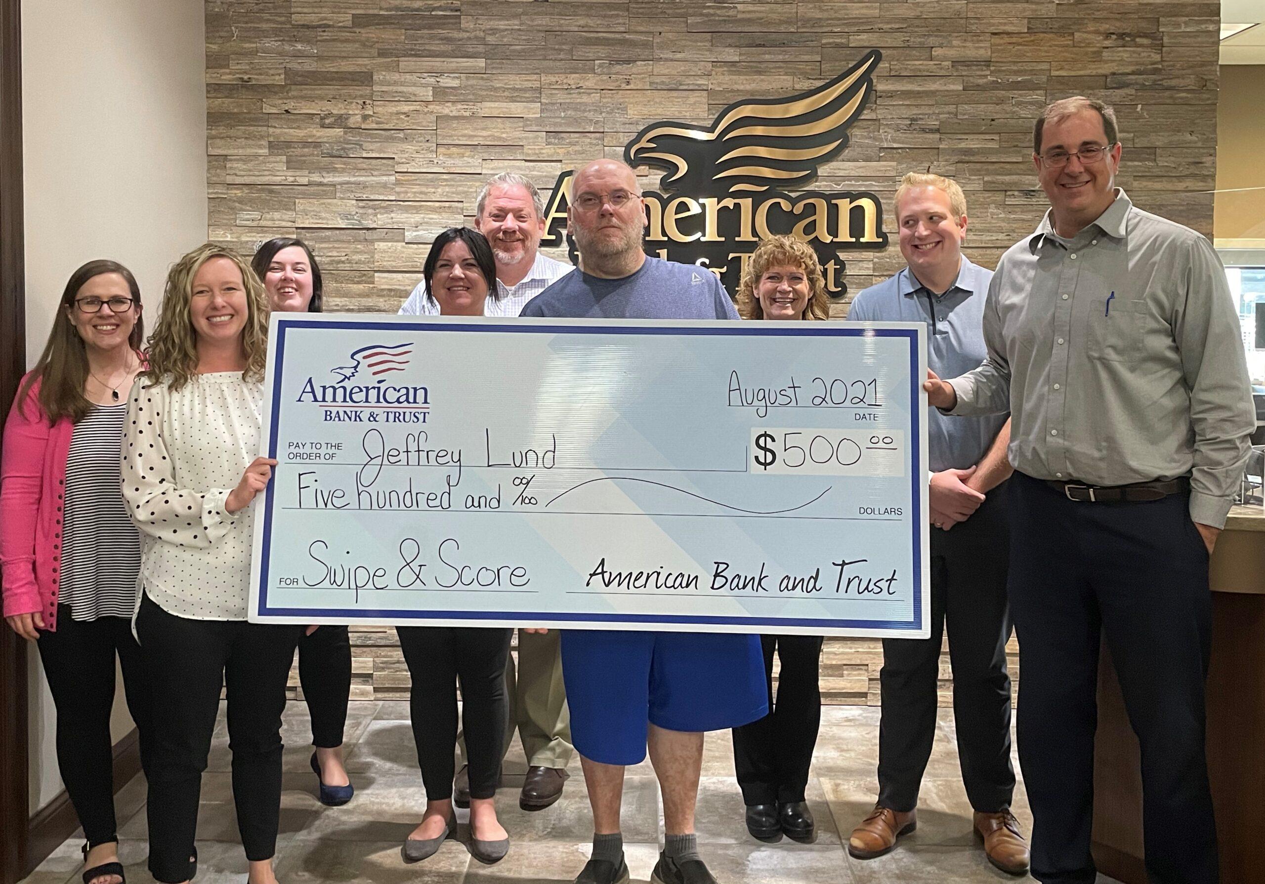 Jeff Lund holding $500 check
